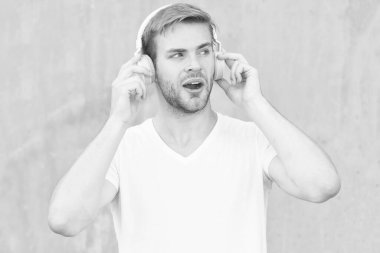 What a pure sound in phonics. Handsome guy listen to sound track. Surprised man enjoy music in earphones. Sound and music technology. Hi-Fi stereo sound. Modern life. Lets jam out at any volume