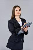 A képességei keresettek. trendi irodai munkás. formális alkalmi divat stílus. stílusos nő tart irodai mappát. A lány kövesse az öltözködési szabályokat. magabiztos üzletasszony dokumentumokkal. elegáns nő kabátban