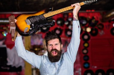 Man with beard and mustache on shouting face holds guitar