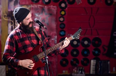 Musician with beard play electric guitar instrument.