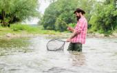 Jel rybařit. vousatý rybář ve vodě. koníček a sportovní aktivita. bušení. letní víkend. Velká rybaření. Rybář s prutem. zralý muž rybaří. muž lovící ryby