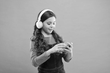 Play game. Subscription channel. Enjoy music concept. Music application. Best music apps for free. Enjoy perfect sound. Girl child listen music modern headphones and smartphone. Listen for free