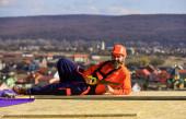 Bauarbeiter setzen Säge ein. professionelle Meister Reparatur Dach. Flachdachinstallation. Dachdecker in spezieller Schutzkleidung. Neues Dach im Bau Wohnhaus