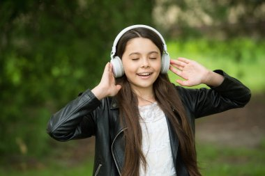 Shes ear for music. Happy child wear ear phones outdoors. Small girl listen to music in headphones. Comfortable ear pads. Ear protective devices. Hearing protection. New technology. Modern life
