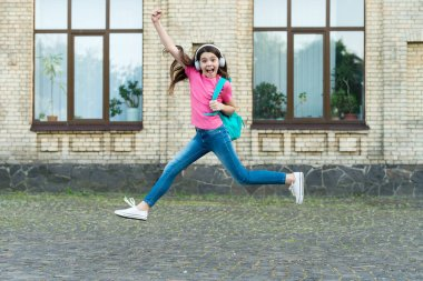 Energetic drive. Happy child in energetic jump outdoors. Energetic mood. Music and entertainment. School holidays. Summer vacation. Healthy and energetic