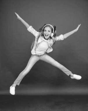 childhood happiness. happy kid listen music. freedom and success. Little girl in earphones. reach her dream. fly up in air. going crazy. excited small girl wear headset. dance with favorite song