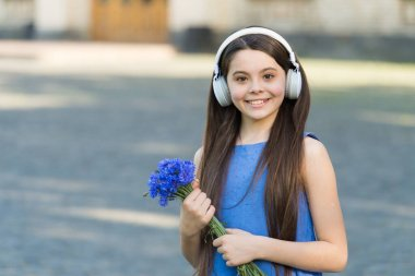 Summer music festival. Happy child listen to music outdoors. Little girl wear headphones playing music. Concert and music performance. New technology. Modern life. Summer holidays