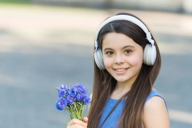 Baby headphones. Happy child wear headphones outdoors. Small girl listen to music in headphones. Noise cancelling headphones. Ear protective devices. Hearing protection. New technology