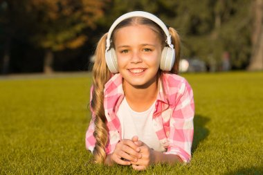 new technology for kids. happy childhood memories. listening to music. back to school. kid study in park. relax on green grass in headphones. small girl listen audio book