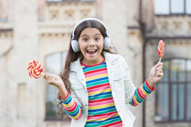full of happiness. happy schoolgirl in stylish hipster outfit. childhood happiness. kid in digital earphones. small girl listen music with lollipop. back to school. small girl eating sweet candy