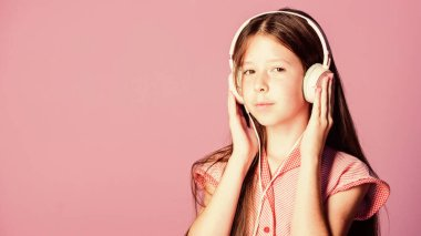 Concentrated teenager. small girl pupil in headphones. girl listen to music. Audio book. back to school. study online. E learning with ebook. self education. Mp3 player. home schooling. copy space