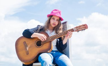 free music content. Teenage musician playing guitar. Portrait of little kid playing guitar on sky background. summer romantic playlist. Guitarist entertaining guests at party. small music lover