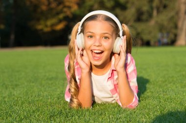 small girl listen audio book. new technology for kids. happy childhood memories. listening to music. back to school. kid study in park. relax on green grass in headphones. Hooked On Learning.