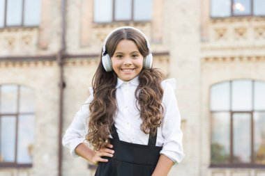 happy schoolgirl in stylish uniform. childhood happiness. kid in digital earphones. small student girl listen music outdoor. back to school. small girl looking smart and intelligent