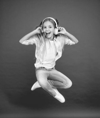 Never ending joy. I believe i can fly. Girl listening music modern gadget. Kid happy with wireless headset dancing jumping. Stereo headphones. Kid using modern technology. Modern child. Perfect sound