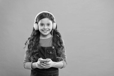 Small girl child listen music modern headphones and smartphone. Online entertainment. Free music apps. Listen for free. Get music account subscription. Enjoy music concept. Enjoy perfect sound