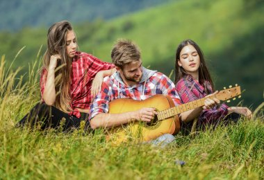 Friends hiking with music. Singing together. Musical pause. Hiking entertainment. People relaxing on mountain top while handsome man playing guitar. Peaceful place. Melody of nature. Hiking tradition