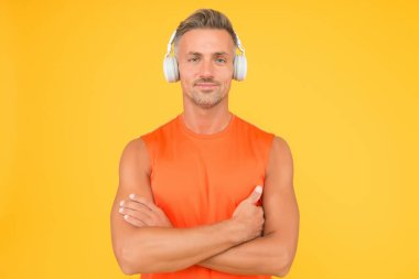 Healthy sportsman or athlete. Sport and fitness. Music for fitness. Sportsman listen music. Sportsman training. Regular workout. Mature coach. Strong sportsman wear headphones and fitness uniform