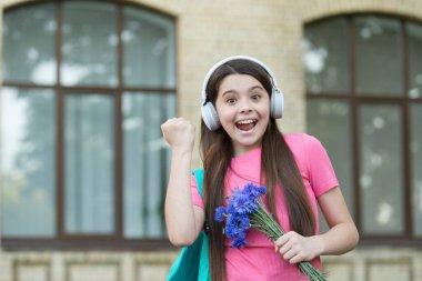Right way to celebrate. Happy child make winner gesture. Little girl hold flowers listening to music. Anniversary celebration. Birthday celebration. Holiday celebration. It calls for celebration