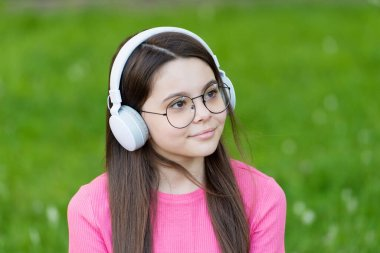 Feel the sound. Little child listen to sound track summer outdoor. Small girl enjoy music playing in earphones. New technology. Modern life. Hi-Fi stereo sound. Its flow of sound