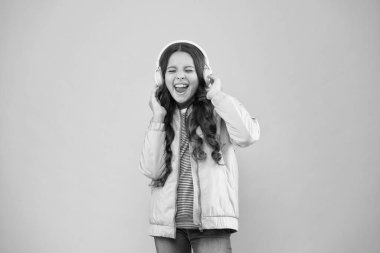 full of emotions. Little child do vocal on song. Emotional singer. Enjoying song playing in headphones. Karaoke and entertainment. Joining in a song. Small girl sing to song pink background