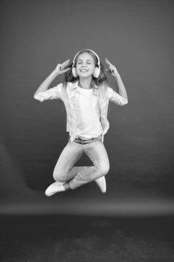 Modern child. Perfect sound. Never ending joy. So much fun. Girl listening music modern gadget. Kid happy with wireless headset dancing jumping. Stereo headphones. Kid using modern technology