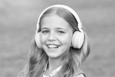 Music is life. Happy child listen to music outdoors. Little girl wear headphones playing music. Music lesson. New technology. Modern life. Listen and learn. Fun and entertainment