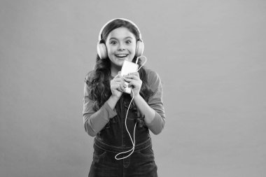 she is so happy. happy little girl. schoolgirl use digital device. casual fashion for kids. kid long hair listen music in headset. small child make play list on smartphone. small girl use mp3 player