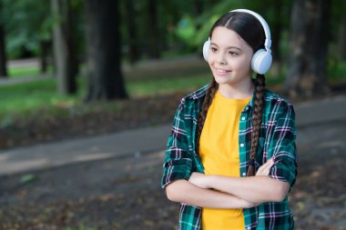 Awesome travel technology. Little girl listen to music in woods. Small child wear headphones in casual style. New technology. Wireless technology. Modern life. Just sync up and go, copy space