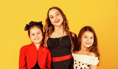 Our family. Happy family. Fashion little girls smile yellow background. Small children with beauty look. Sisters or female siblings. Family day. Together we make family