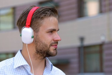 Young man listening music with headphones on urban background, defocused.