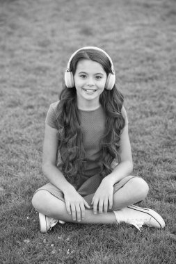 Educational podcast. Kid girl enjoy music green grass meadow. Pleasant time. Child headphones listen music. Girl headphones listening music. My summer playlist. Listen music while relaxing outdoors