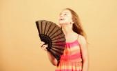 Kühlung und Belüftung. Sommerhitze. Frische Luft. Mädchen fächelt sich mit Fächer auf. Klimaanlage. Klimakontrolle. Klimaanlage. Winken, um aktuelle Luft zu schaffen. Kleines Mädchen schwenkt eleganten Fächer