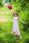 Nové květiny. ohromující dívka s kyticí květin růží. šťastné dítě v slamáku. Přírodní účes. Den matek. Šťastný den žen. Portrét malého dítěte s květinami. láska a krása