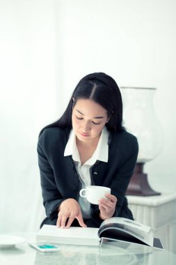 Young businesswoman sitting at table in coffee shop and reading