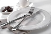 classic table setting cutlery knife and fork on porcelain plate, linen cloth, bowl of chocolate pieces and cup with saucer on white background