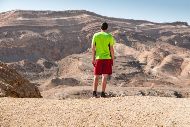 Traveler man is the Negev desert. beautiful desert landscape and concept of freedom and happiness, heathy lifestyle.