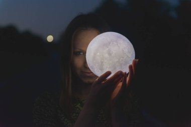 A girl with a moon in her hands