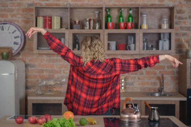 Woman dancing in the kitchen - view from the back