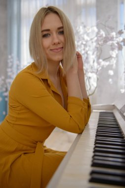Pretty Woman in a yellow dress sitting at the piano
