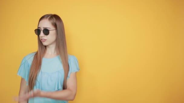 Mädchen Brünette in blauem T-Shirt über isoliertem orangefarbenem Hintergrund zeigt Emotionen