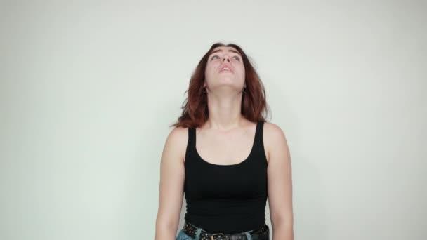 schönes Mädchen in schwarzem Tank-Top über isoliertem weißem Hintergrund zeigt Emotionen