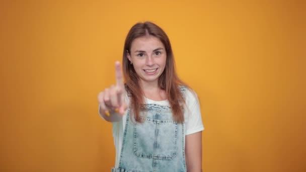Mladá žena na bílém tričku, nad oranžovým pozadím vykazuje emoce