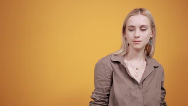 Blondes Mädchen in brauner Bluse über orangefarbenem Hintergrund zeigt Emotionen