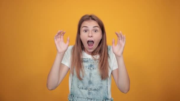 Young woman wearing white t-shirt, over orange background shows emotions