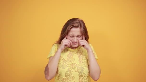 Brünettes Mädchen in gelbem T-Shirt über orangefarbenem Hintergrund zeigt Emotionen