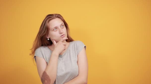 brunette girl in gray t-shirt over isolated orange background shows emotions