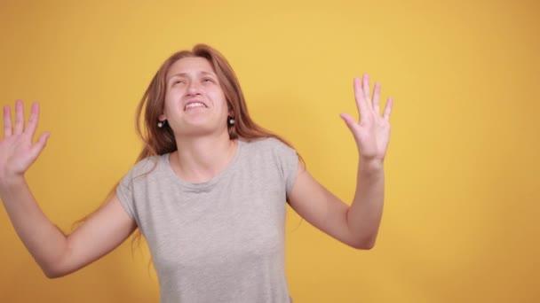 brunetka v šedém tričku nad ojedinělým oranžovým pozadím vykazuje emoce