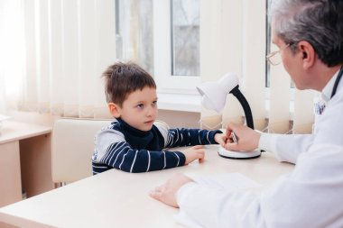 A young boy is listened to and treated by an experienced doctor in a modern clinic. A virus, and an epidemic
