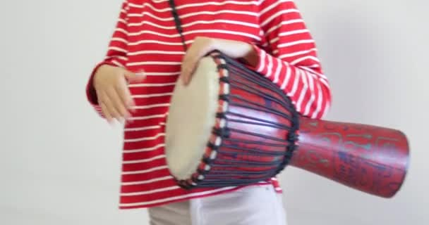 attractive body of female drummer playing the djembe, African instrument. the cute woman is wearing red striped top clothe. White Background